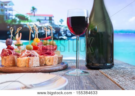 Set of Spanish tapas served on a sliced baguette with red wine on wooden table against the sea