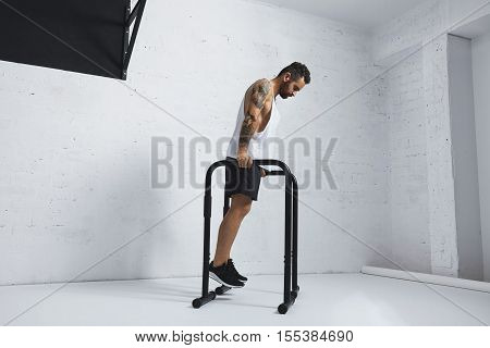 Strong tattooed in white unlabeled tank t-shirt male athlete shows calisthenic moves Holding position on parallel bars before classic dips, looking on floor