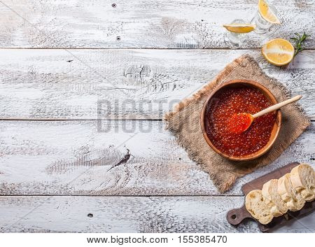 Red caviar in a wooden bowl on old wooden table. Top view