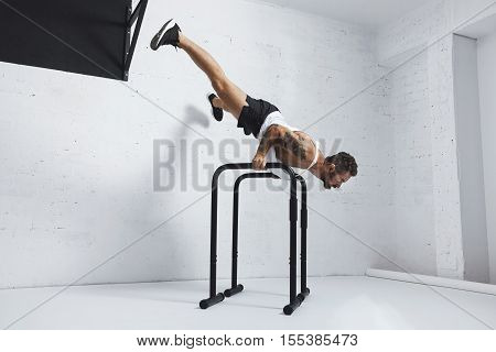 Strong tattooed in white unlabeled tank t-shirt male athlete shows calisthenic moves Extended legs planche push ups on parallel bars