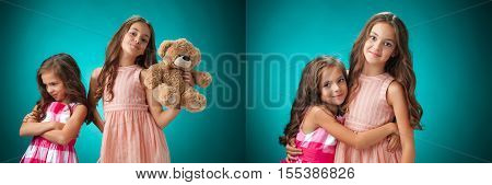 The two cute little girls on blue background with Teddy bear. The concept of a quarrel and reconciliation