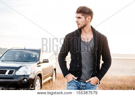 Pensive young man standing on the beach with car on background