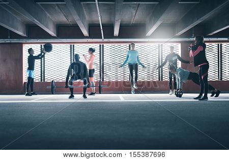 Group of people exercising together lifting weight using skipping rope and medicine ball