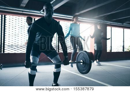 Black man exercising lifting weight working out with group of friends in urban environment