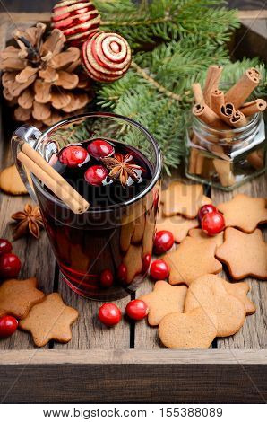 Christmas mulled wine. Holiday concept decorated with Fir branches, Gingerbread Cookies and Cranberries on dark wooden tray.