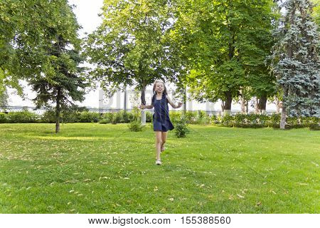 Cute running European girl with disheveled hair in green park