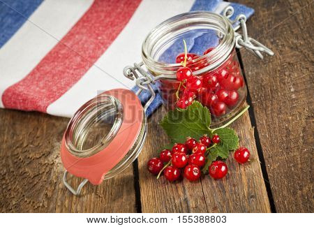 redcurrant berries in a jar with kitchen towel on rustic wooden table, tilted view