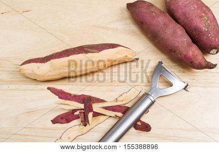 Peeling sweet potato A sweet potato being peeled on a wooden chopping board