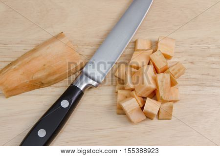 Diced sweet potato A sweet potato being diced on a wooden chopping board