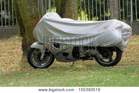 BERLIN GERMANY. SEPTEMBER 2ND 2016 - A parked motorcycle with protective cover in a backyard