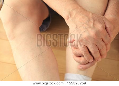Man sitting on floor with both hands on a leg