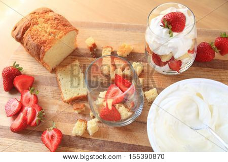 Overhead of strawberries whipped cream and pound cake with finished miniature trifle on cutting board