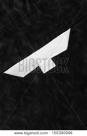 Blank white clothes label on black lacy cloth as a background