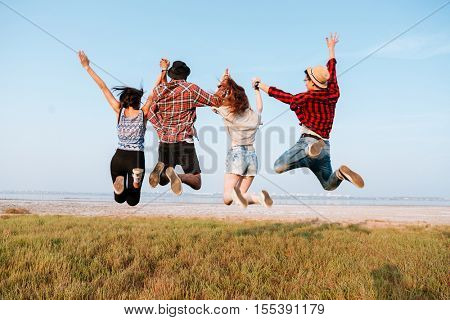Back view of happy excited young people holding hands and jumping in the air outdoors