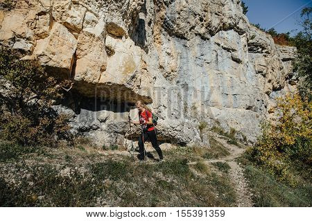Yalta Russia - October 6 2016: young woman runner with walking poles running trail on background of rocks during Crimea mountain marathon