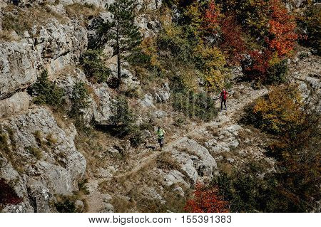 Yalta Russia - October 6 2016: two men skyrunner with walking poles going on a trail through autumn forest during Crimea mountain marathon