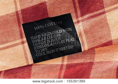 Fabric composition and washing instructions label on plaid red cloth