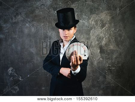 Illusionist man with cards fan on a dark background.
