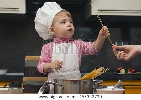little cute child helps her mother cook pasta