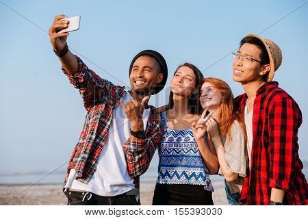 Multiethnic group of cheerful young people standing and making selfie with cell phone outdoors