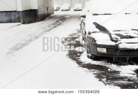 Car under a pile of snow mixed snow and sleet weather conditions. Outdoor cropped shot