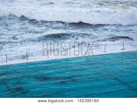 Closeup of saltwater pool and ocean waves. Saltwater pools are commonly built near the sea in Australia