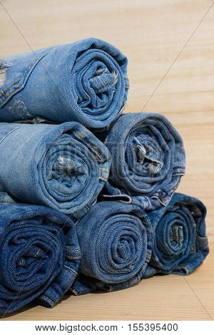 Rolled jeans stack with wooden board
