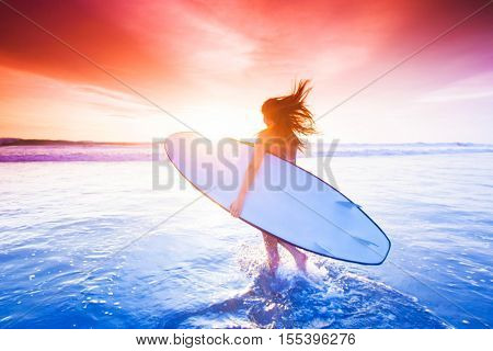 Beautiful sexy surfer girl on the beach at sunset