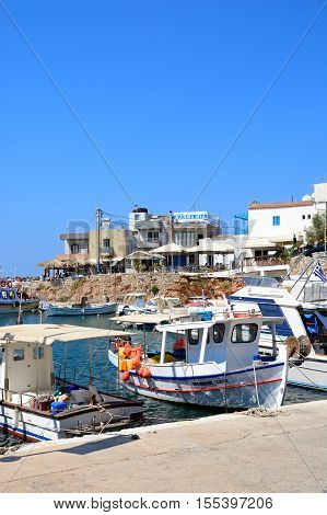 SISSI, CRETE - SEPTEMBER 14, 2016 - Traditional Greek fishing boats moored in the harbour with bars and restaurants to the rear Sissi Crete Greece Europe, September 14, 2015.