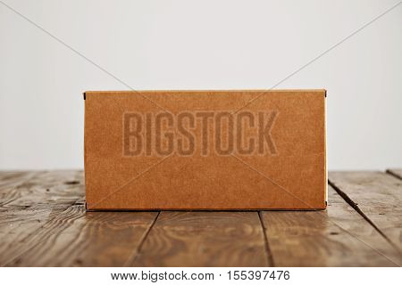 Craft blank cardboard package box presented on stressed brushed wooden table, isolated on white background
