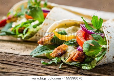 Kebab in a pancake with vegetables on old wooden table
