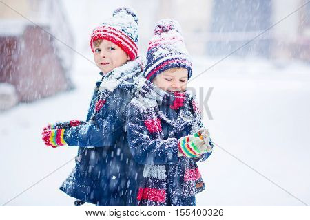 Two little kid boys in colorful clothes playing outdoors during snowfall. Active leisure with children in winter on cold days. Happy siblings and twins having fun with snow