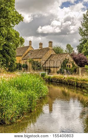 River Eye and historic cottages at Lower Slaughter said to be prettiest village in England and tourist destination.
