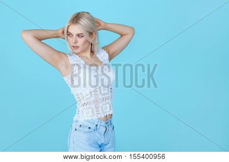 pretty elegant girl posing over blue background with copy space. Young blond woman wearing lace t-shirt isolated over color wall