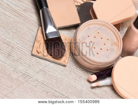 Various makeup products and accessories to even out skin tone and complexion. Concealers, foundation, powder, brushes, sponges on shabby wooden surface. Copy space poster