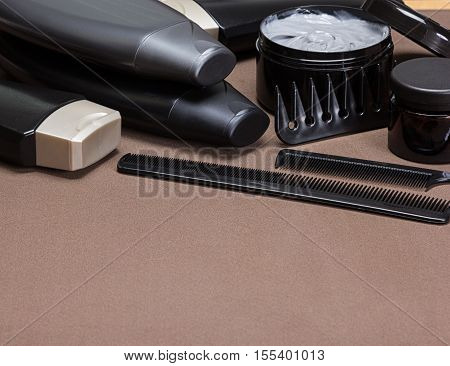 Different hair care and styling products and accessories. Cosmetics and various kinds of combs on brown textured surface. Shallow depth of field. Copy space
