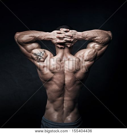 Strong athletic mans back on dark background. The concept of a complex imbroglio.