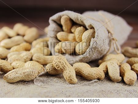 peanuts   untreated in sack on wooden background