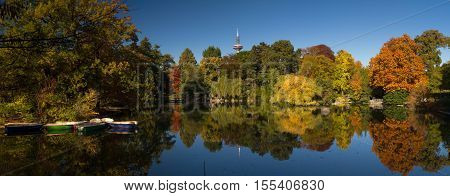 Trees in autumn reflecting in a pond under a blue sky Frankfurt am Main Germany