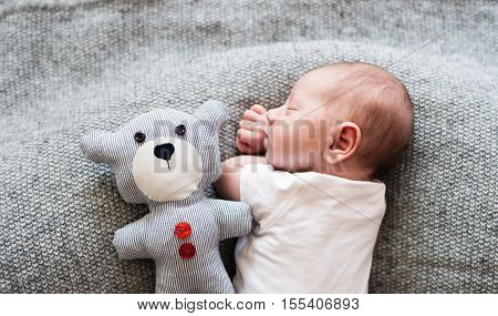 Cute little newborn baby boy lying on bed with his teddy bear, sleeping, close up