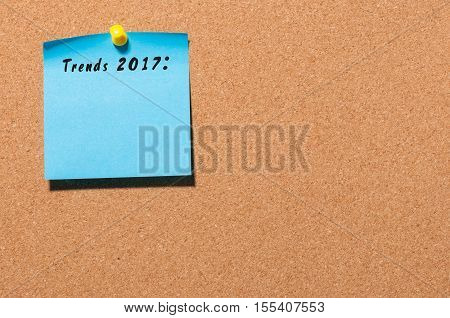 Trends 2017 written on blue sticker pinned at cork notice board with empty space for text. Business concept.