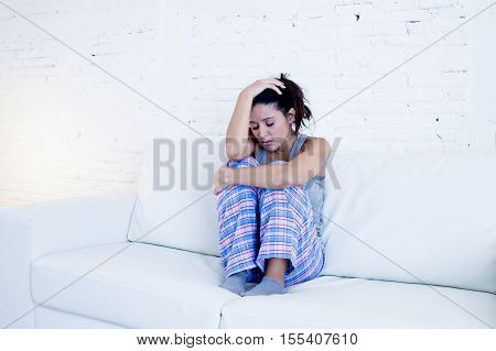 young beautiful hispanic woman in painful expression suffering menstrual period pain lying sad on home sofa couch having tummy cramp in female health concept poster