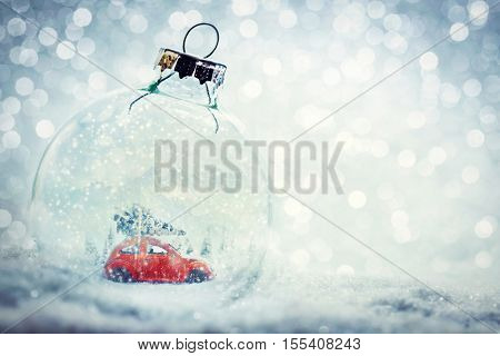 Christmas glass ball in snow with miniature winter world inside - car with Christmas tree, mountains. Glitter background.