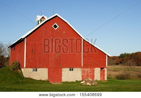 A small red barn and a woodpile on a Wisconsin farm.