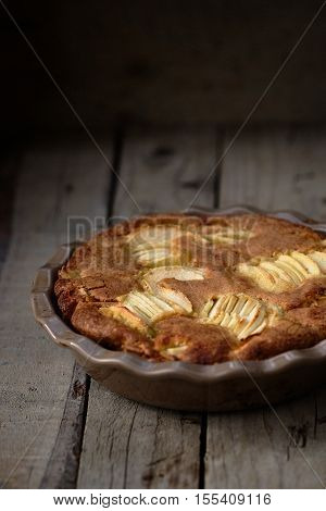 Rustic french apple cake with vanilla and rum in a round ceramic baking pan. Wooden background.