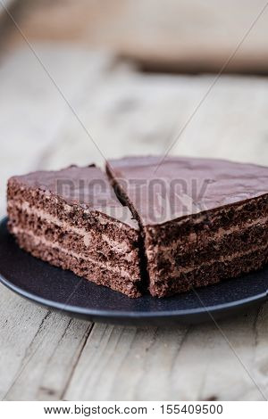 Cut of chocolate layer cake with chocolate cream and glaze. Wooden background
