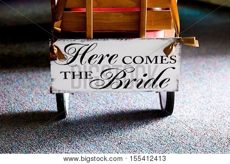 Sign on wagon for wedding ceremony reads here comes the bride
