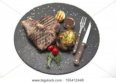Juicy beef steak medium rare on a stone baked potatoes and barbecue sauce and large sea salt with fork and knife