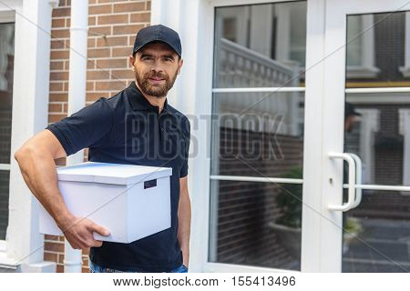 postman standing with a package in front of the street door