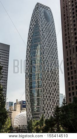 Tokyo Japan - October 2 2016: The glass-and-iron iconic Cocoon-shaped tower or Tokyo Mode Gakuen from top to bottom under light blue sky. Green foliage and other towers. Shinjuku neighborhood.
